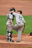 Dayton Dragons pitcher Ismael Guillon (35) leans on catcher Joe Hudson (8) while cleaning his cleats from the mud during a game against the Lake County Captains on June 8, 2014 at Classic Park in Eastlake, Ohio.  Lake County defeated Dayton 4-2.  (Mike Janes/Four Seam Images)