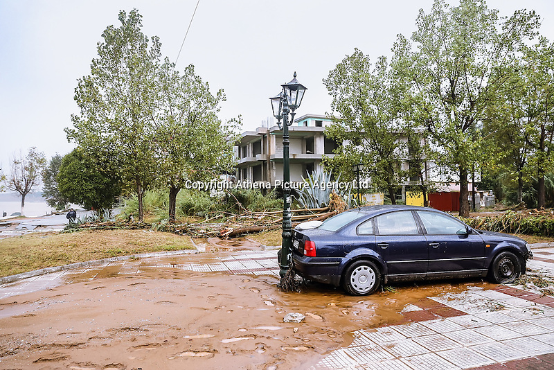 A car rests against a street light after being shifted by flood water in Nea Mihaniona