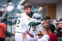 Mesa Solar Sox designated hitter Eli White (21), of the Oakland Athletics organization, is congratulated by teammates in the dugout during an Arizona Fall League game against the Peoria Javelinas at Sloan Park on October 11, 2018 in Mesa, Arizona. Mesa defeated Peoria 10-9. (Zachary Lucy/Four Seam Images)