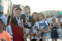 SARANSK, RUSSIA - June 25, 2018: A Russia family poses for a selfie while walking down Kommunisticheskaya Ulitsa to attend the 2018 FIFA World Cup group stage match between Iran and Portugal at Mordovia Arena.