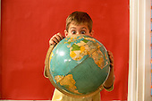MR / Schenectady, NY. Yates Arts in Education Magnet Elementary School. Grade 1. Portrait of student (boy, 6) with surprised expression behind earth globe. MR: Bri4. ID: AJ-LC. © Ellen B. Senisi