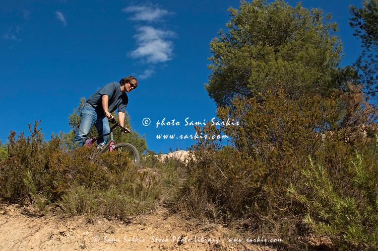 Man riding his mountain bike on a dirt path through bushes, Vitrolles, Provence, France.