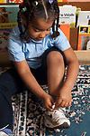 Preschool 3-4 year olds independence skills girl tying her own shoe vertical