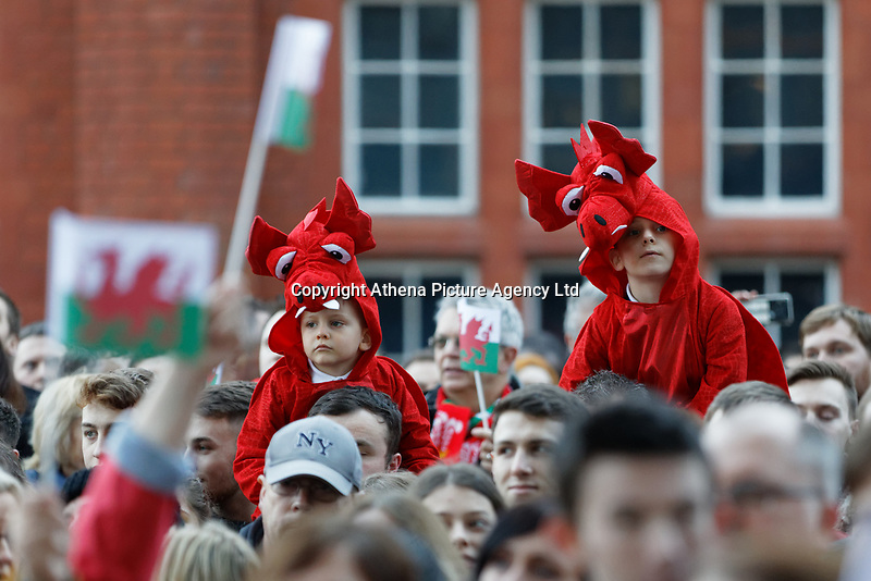 Two young rugby fans wearing dragon outfits look on during the Celebration for Wales Six Nations Win at the National Assembly for Wales, Cardiff Bay, Wales, UK. Monday 18 March 2019