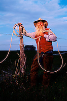 A cowboy rancher smiles as he leans against a fence and holds his roping lariat. South Dakota.