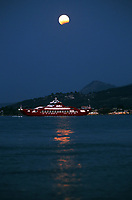 A full moon with a partial eclipse, rises while a ferry boat arrives from Eretria to Oropos in the Evia Bay, 30 miles east of Athens, Greece. Monday 07 August 2017