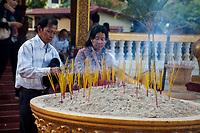 Cambodia, Siem Reap.  Worshipers Placing Incense at Preah Ang Chek and Preah Ang Chorm Temple.