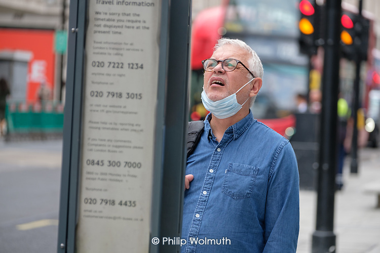 Man with mask checks a bus stop timetable.  Midweek shoppers in Oxford Street London following the easing of Covid-19 lockdown measures.