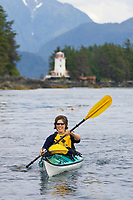Kayaker paddles Sitka sound near the Rockwell lighthouse, a famous historical icon of the coastal town of Sitka, Alaska in Alaska's southeast panhandle.