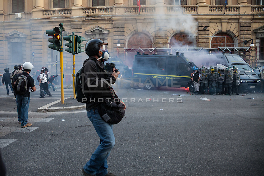 A press photographer reporting during the storm of the entrance of the Ministry of Economy. The building is attacked by a group of rioters, some of whom threw crude homemade explosive devices and others who took part in acts of vandalism.  Oct. 19, 2013. (Photo by Riccardo Budini / UnFrame)