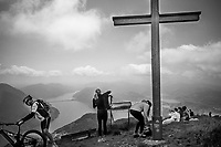Switzerland. Canton Ticino. View from Monte Boglia to the lake and the city of Lugano. Hikers and a cyclist with his mountain bike stand close to a  wooden cross erected at mountain peak. Rocky view point with a map. Monte Boglia (also known as Colma Regia) is a mountain whose peak is along the border of Ticino, Switzerland and Lombardy, Italy. It reaches an elevation of 1,516 metres and overlooks Lake Lugano on its southern side. Lake Lugano (Italian: Lago di Lugano or Ceresio) is a glacial lake which is situated on the border between southern Switzerland and Northern Italy. 31.05.2020 © 2020 Didier Ruef