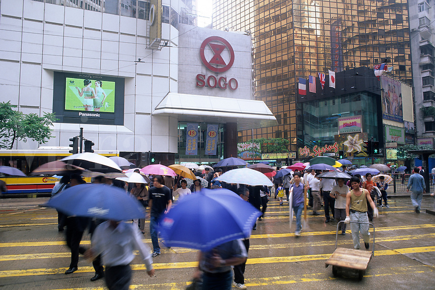 Hustle and bustle of business people with umbrellas in the Central District of Hong Kong in todays modern business climat