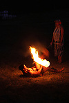 Hawaiian Fire Dancer performing at night laying down twirling a fire stick and is in a dangerous position.  Someone stands by for safety