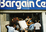 A store is looted in Korea Town during the 1992 Rodney Kings Riots in Los Angeles near Vermont  Avenue and Second Street as police observed from the safety of the grocery store parking lot diagonally across the intersection. Photo Jim Mendenhall/Los Angeles Times.