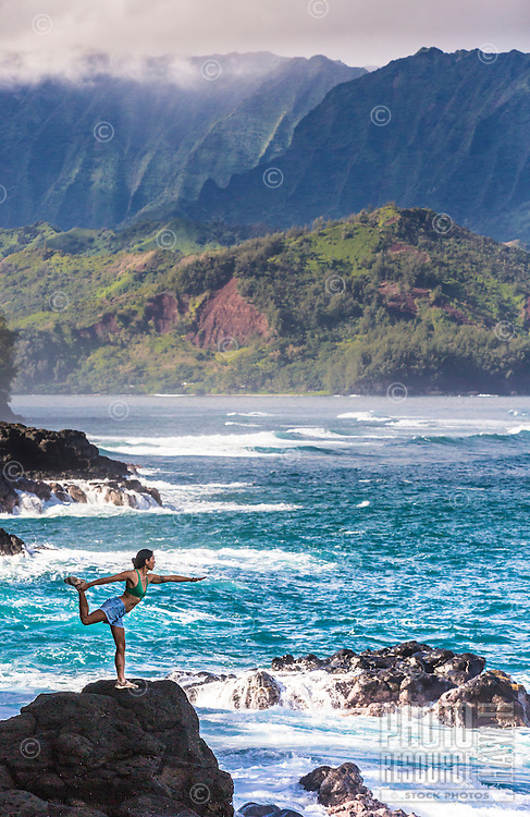 A woman holds a yoga pose on a rocky shore while waves break around her, Hanalei Bay, Kaua'i.
