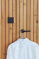 A crisp white shirt hangs from a hanger on a door handle in the wood-clad wall of the master bedroom
