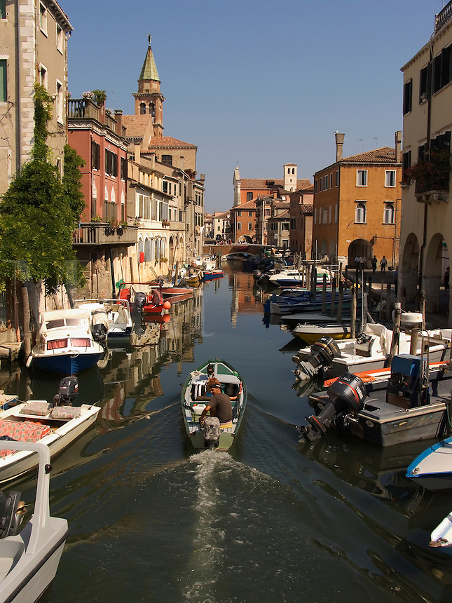 Motorboat cruises past fishing boats and houses along Vena canal in Chioggia Ital