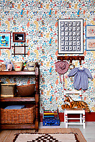 The 'Alice in Wonderland' wallpaper makes a great backdrop for a collection of children's toys, clothing and storage baskets