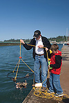 Grandfather & grandson catching crab on dock at the Embarcadero in Newport on the central Oregon Coast..06061533