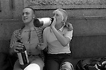 Skinhead couple drinking cider. London England. 1980s. Skinheads tattoo and image of Christ as a skinhead on his chest.