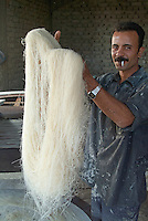 Portrait of a man showing off the noodles that he is making in his small factory, Al-Qusair, Egypt.