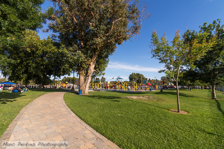 A new paver pathway curves underneath mature trees on its way to a giant playground.  The park is full of people on this sunny day.