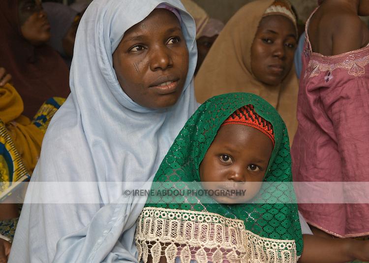 A Fulani woman and child in the Tudun-Murtala area of Kano, Nigeria wear traditional Muslim headwear.