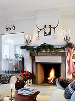The fireplace in the sitting room has been inspired by a traditional French model, made festive and cheerful with candelabra and Christmas garlands