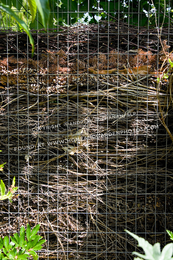 """A close up detail showing layers in a portion of a compost fence in a residential garden.  Made up of two layers of sturdy wire mesh screen held roughly 6-8"""" apart, the home gardener places clippings and waste in the open top of the fence and allows them to fall to the bottom.  Subsequent layers build up in the fence, while the earlier clippings decompose and becomes usable compost to be removed from the bottom."""