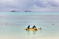 Children play in a small boat on the waters of the Funafuti lagoon. In the background, international fishing vessels stop to refuel and restock before continuing to fish the waters around Tuvalu. Located in the South West Pacific Ocean, Tuvalu is the world's 4th smallest country and is one of the most vulnerable to climate change impacts including sea level rise, drought and extreme weather events. Tuvalu - March, 2019.