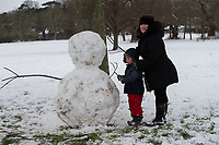 A young family make a snowman following snowfall at Foots Cray Meadow, Sidcup, Kent, England on the 9 February 2021. Photo by Alan Stanford.