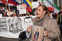 """250 bis 300 Menschen demonstrierten am Samstag den 31. Oktober 2015 in Berlin fuer die Unterstuetzung des syrischen Diktators Assad durch Russland. Sie trugen Fahnen Syriens, der ehemaligen Sowietunion, Russlands, Nordkoreas, der DDR, des Iran und Venezuelas, die sich """"alle zusammen gegen den Imperialismus zur Wehr setzen"""" wuerden. Russlands Praesident Putin wurde ausdruecklich fuer sein Militaerengagement gedankt, das Eingreifen der USA verurteilt.<br /> Im Bild: Eine Demonstrantin mit einem Portraitfoto des syrischen Diktators Assad.<br /> 31.10.2015, Berlin<br /> Copyright: Christian-Ditsch.de<br /> [Inhaltsveraendernde Manipulation des Fotos nur nach ausdruecklicher Genehmigung des Fotografen. Vereinbarungen ueber Abtretung von Persoenlichkeitsrechten/Model Release der abgebildeten Person/Personen liegen nicht vor. NO MODEL RELEASE! Nur fuer Redaktionelle Zwecke. Don't publish without copyright Christian-Ditsch.de, Veroeffentlichung nur mit Fotografennennung, sowie gegen Honorar, MwSt. und Beleg. Konto: I N G - D i B a, IBAN DE58500105175400192269, BIC INGDDEFFXXX, Kontakt: post@christian-ditsch.de<br /> Bei der Bearbeitung der Dateiinformationen darf die Urheberkennzeichnung in den EXIF- und  IPTC-Daten nicht entfernt werden, diese sind in digitalen Medien nach §95c UrhG rechtlich geschuetzt. Der Urhebervermerk wird gemaess §13 UrhG verlangt.]"""