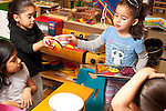 Education Preschool 4 year olds pretend play area two girls both trying to hold bowl dispute watched by another boy and girl