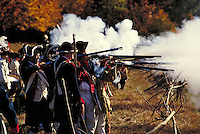 Defenders with muskets behind light fortification fires volley; view down line of defenders; gunsmoke; drummers stand behind. New York USA Pound Ridge Reservation.