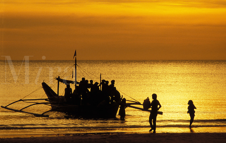 The Philippines.  traditional outrigger boat silhouetted against the setting sun, with many passengers..