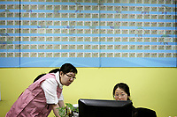 CHINA. Beijing. Visas to Canada plaster the walls inside the offices of Aoji, an organisation which assists Chinese students in language training and placing them in overseas universities throughout the world. 2010