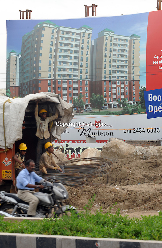 Workers on truck in front of new high rise apartment blocks advert in Madras, India