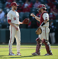 Arkansas starter Caleb Bolden (left) receives the ball Wednesday, April 7, 2021, from catcher Dylan Leach during the fourth inning of the Razorbacks' 10-3 win over UALR at Baum-Walker Stadium in Fayetteville. Visit nwaonline.com/210408Daily/ for today's photo gallery. <br /> (NWA Democrat-Gazette/Andy Shupe)