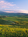 Tuscany, Italy, <br /> Evening light on farms and green rolling hills of Val d'Orcia beneath the distant Mount Amiata - from the hill town of Pienza