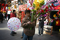 CHINA. A man using his cellphone during Chinese New Year in Ditan Park in Beijing.  Chinese New Year, or Spring Festival, is the most important festival and holiday in the Chinese calendar In mainland China, many people use this holiday to visit family and friends and also visit local temples to offer prayers to their ancestors. The roots of Chinese New Year lie in combined influences from Buddhism, Taoism, Confucianism, and folk religions.  2008
