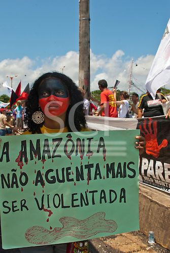 """Belem, Para State, Brazil. Demonstration against the construction of the Belo Monte hydroelectric dam, 20th August 2011. Woman with hand-written sign """"A Amazônia não aguenta mais ser violentada""""."""