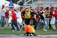 Maryland fans charge the field to celebrate with the Terrapin players, as New Mexico goalkeeper Mike Graczyk (foreground) laments his team's loss. The University of Maryland defeated the University of New Mexico 1-0 in the NCAA Final at SAS Stadium in Cary, North Carolina, Sunday, December 11, 2005.