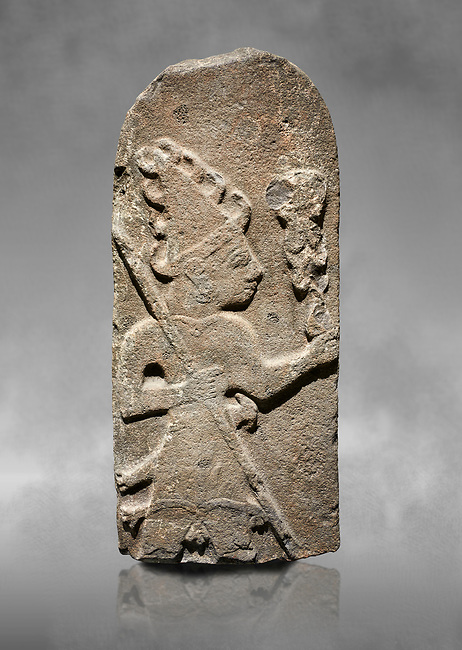 Hittite monumental relief sculpture ofa God probably holding lightning rods. Late Hittite Period - 900-700 BC. Adana Archaeology Museum, Turkey. Against a grey art background