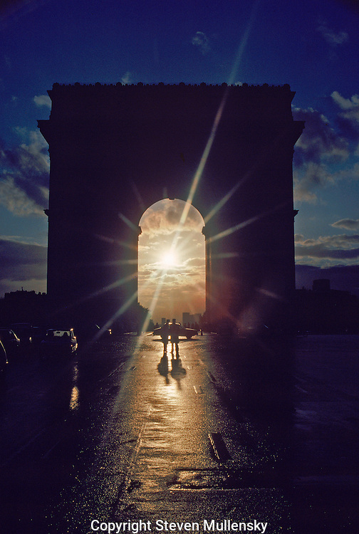 The Arc du Triomph is one of the most famous landmarks in Paris, France. Here the setting sun is framed between the uprights and a pair of French policemen are standing guard while waiting for a foreign dignitary to leave the Elysee Palace.