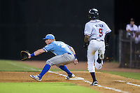 Chris DeVito (34) of the Burlington Royals stretches for a throw as Isranel Wilson (9) of the Danville Braves runs towards first base at American Legion Post 325 Field on August 16, 2016 in Danville, Virginia.  The game was suspended due to a power outage with the Royals leading the Braves 4-1.  (Brian Westerholt/Four Seam Images)