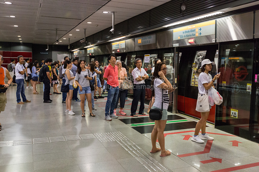 Singapore MRT Mass Rapid Transit Passengers waiting to Board Arriving Train.