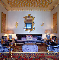 A sofa and chairs upholstered in indigo silk velvet with mauve cushions creates an opulent aesthetic