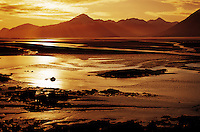 Sunset landscape of the Tumagin Flats with mountains rising in the background. Alaska.