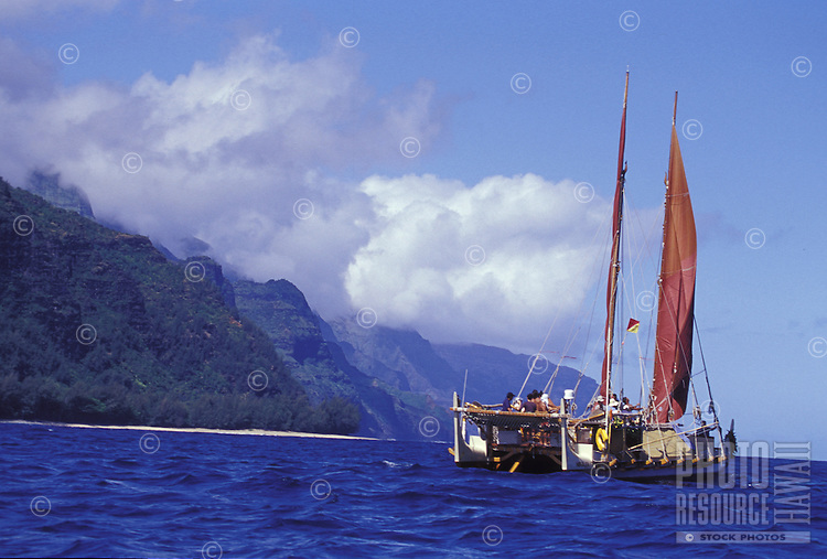 Hokulea, a traditional double hulled Hawaiian sailing canoe, sets sail off the Na Pali Coast for the voyage to the Northwestern Hawaiian Islands