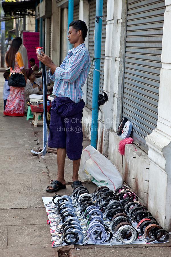 Myanmar, Burma, Yangon.  Sidewalk Belt Salesman.